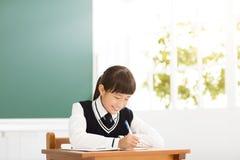 愉快的少年女孩研究在教室 免版税图库摄影