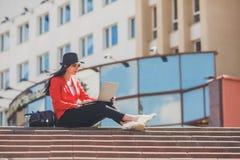 愉快的工作在膝上型计算机outdors的行家少妇 使用膝上型计算机的学生女孩在大学 被定调子的图象 免版税库存照片