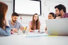 愉快的工友谈论在会议在创造性的办公室 免版税库存照片