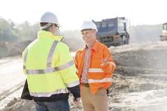 愉快的工程师谈话与同事在建造场所在晴天 库存照片