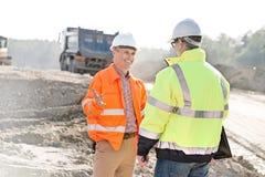愉快的工程师谈话与同事在建造场所在晴天 免版税库存图片