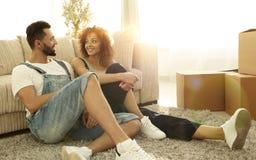 愉快的已婚夫妇坐在一栋新的公寓的地毯 免版税库存照片