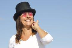 愉快的帽子佩带的妇女天空背景 免版税库存照片