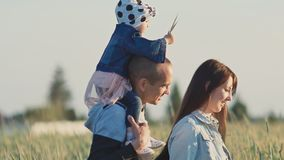 愉快的年轻三口之家人一起在一块麦田在绿色小尖峰中的 一个小女儿坐 影视素材