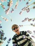 愉快的年轻亚洲人看下来入在淡紫色领域的照相机 库存图片