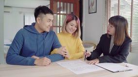 愉快的年轻亚洲夫妇和地产商代理 签署有些文件的快乐的年轻人,当坐在书桌与他的妻子一起时 股票视频