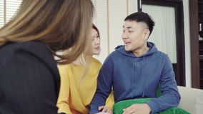愉快的年轻亚洲夫妇和地产商代理 签署有些文件的快乐的年轻人,当坐在书桌与他的妻子一起时 股票录像