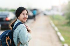 愉快的年轻亚裔妇女画象穿蓝色牛仔布的夹克 免版税库存图片