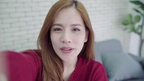 愉快的年轻亚裔妇女采取selfie的和录影在家叫与智能手机 影视素材