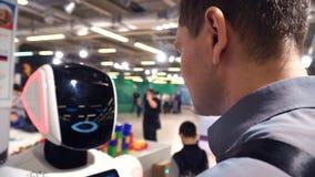 愉快的年轻人与机器人沟通 有照相机关闭的机器人头 商展 股票录像