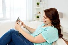 愉快的年轻人加上有片剂个人计算机的大小妇女在家 库存照片