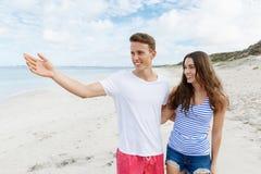 愉快的年轻人和妇女结合一起走在海滩 图库摄影