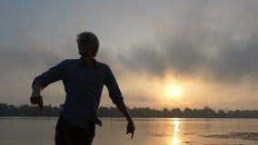 愉快的年轻人在河岸转过来在精采日落在Slo Mo 股票视频