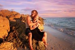 愉快的年轻人已婚夫妇坐多岩石的海滩由海洋a 免版税库存照片