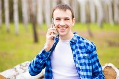 愉快的年轻人的图象走在城市公园和谈话由电话 免版税库存照片