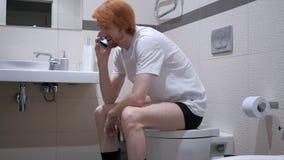 愉快的年轻人谈话在洗手间,洗脸台的电话 库存照片