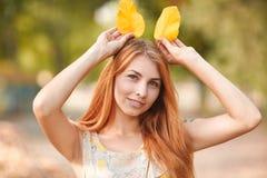 愉快的年轻人,美丽的红发女孩在秋天公园 免版税库存照片