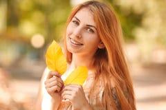 愉快的年轻人,美丽的红发女孩在秋天公园 库存照片