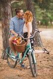愉快的年轻加上自行车在乡下 免版税库存照片