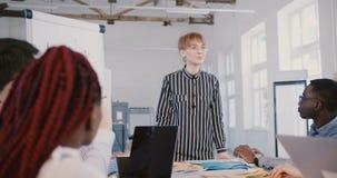 愉快的年轻千福年的女性办公室实习生工作者谈话与不同种族的队在公司职员会议上在coworking 股票录像