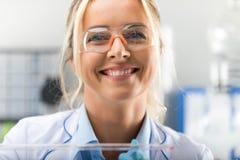 愉快的年轻可爱的微笑的妇女科学家在实验室里 免版税图库摄影