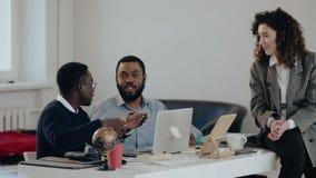愉快的年轻可爱的白种人经理女商人谈话与两个黑人男性同事在现代办公室桌上 股票视频