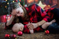 愉快的年轻在家使用在圣诞节期间的母亲和她的儿子 免版税库存图片