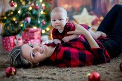 愉快的年轻在家使用在圣诞节期间的母亲和她的儿子 库存图片