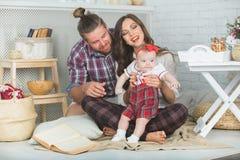 愉快的年轻在家使用在地毯的家庭母亲、父亲和女儿 免版税库存图片