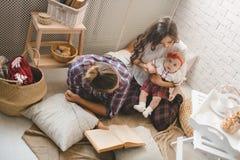 愉快的年轻在家使用在地毯的家庭母亲、父亲和女儿 库存照片