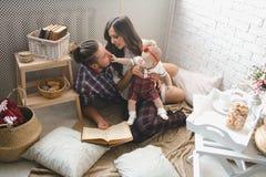 愉快的年轻在家使用在地毯的家庭母亲、父亲和女儿 库存图片