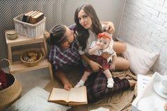愉快的年轻在家使用在地毯的家庭母亲、父亲和女儿 免版税库存照片