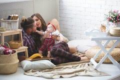 愉快的年轻在家使用在地毯的家庭母亲、父亲和女儿 图库摄影