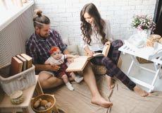 愉快的年轻在家使用在地毯的家庭母亲、父亲和女儿 免版税图库摄影