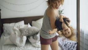 愉快的年轻在家跳舞在床附近的母亲和小逗人喜爱的女儿在卧室 免版税图库摄影