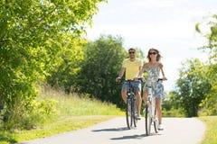 愉快的年轻夫妇乘坐的自行车在夏天 免版税库存照片