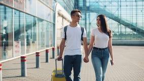 愉快的年轻夫妇同行陪行李在机场或火车站附近 旅行,假期,假日的概念 影视素材