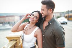 愉快的年轻夫妇听的音乐在耳机的城市在户外 免版税库存图片