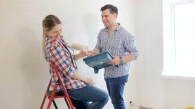 愉快的年轻夫妇慢动作录影获得乐趣,当做整修在他们的新房时 击中的家庭使用和 股票视频