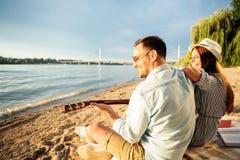 愉快的年轻夫妇有了不起的时光一起在海滩,弹吉他 库存照片