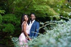 愉快的年轻夫妇画象在有美丽的叶子的一个庭院里 免版税图库摄影
