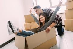 愉快的年轻夫妇获得与纸板箱的乐趣在新房移动的天 库存图片