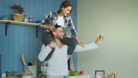 愉快的年轻夫妇获得乐趣和谈网上录影电话在厨房在家 女孩坐男朋友` s脖子 股票录像