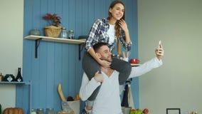 愉快的年轻夫妇获得乐趣在厨房在家 女孩坐男朋友` s脖子,当采取selfie画象的他时 影视素材