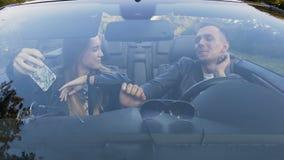 愉快的年轻夫妇获得乐趣在驾驶期间在汽车敞蓬车 股票录像