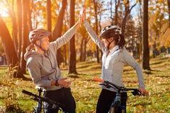 愉快的年轻夫妇获得骑自行车的乐趣在晴朗的秋天天在公园 捉住在背后照明 免版税库存图片