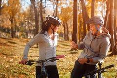 愉快的年轻夫妇获得骑自行车的乐趣在晴朗的秋天天在公园 捉住在背后照明 库存图片