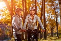 愉快的年轻夫妇获得骑自行车的乐趣在晴朗的秋天天在公园 捉住在背后照明 免版税图库摄影