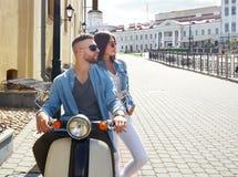 愉快的年轻夫妇骑马滑行车在镇里 英俊的人和少妇旅行 冒险和假期概念 库存照片