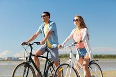 愉快的年轻夫妇骑马自行车在海边 库存图片